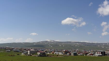 Ardahan, Turkey - May 9, 2019: Panorama Ardahan, Turkey, with green fields and meadows and white, snowy mountains in the background.