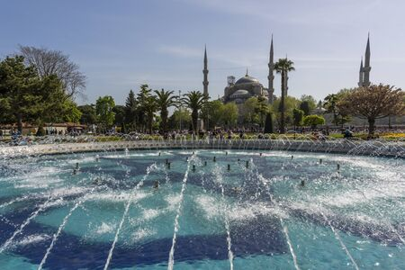 Istanbul, Turkey - April 29, 2019: People on the square and park in the centre of Istandbul with great fountain and Sultan Ahmet Camii in the background.
