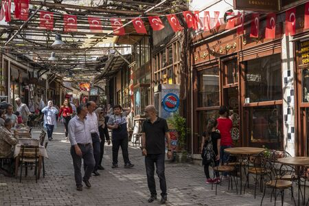 Safranbolu, Turkey - May 1, 2019:  Touristic village with tourists shopping at one of the main streets with restaurants and cafes and with turkish flags.