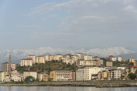 Pazar, Turkey - May 7, 2019: The city of Pazar at the Black Sea with houses, flats and minarets and in the background the snowy mountains of Turkey. Redactioneel