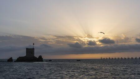 ar, Turkey - May 7, 2019: Sunset at the Black Sea at Pazar, Rize, with castle Kiz sun rays and orange sky.