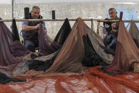 Sinop, Tukey - May 3, 2019: Two fishermen are working on and repairing  fishing nets in the harbor of Sinop.