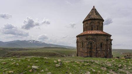 Ani, Turkey - May 9, 2019: Ruins of the old Armenian town Ani with church and in the background snowy mountains, Turkey.