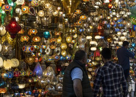 Istanbul, Turkey - April 29, 2019: Lamp shop in the great bazaar in Instanbul with colored lamps packed in the shop and two men. Redactioneel
