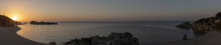 Panorama Beach at Imrenli with rock islands in the Black Sea during sunset with golden light and two people on rock.