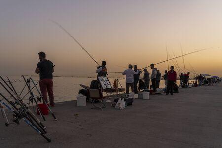 Istanbul, Turkey - April 29, 2019: Fishing men at the bloulevard at the harbor in Instanbul, Turkey.