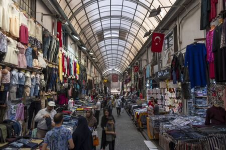 Istanbul, Turkey - April 29, 2019: People in the great bazaar with shops and shopping people, with turkish flags on the walls.