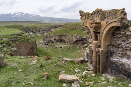 Ani, Turkey - May 9, 2019: Ruins of the old Armenian town Ani with churches and snowy mountains in the background, Turkey.