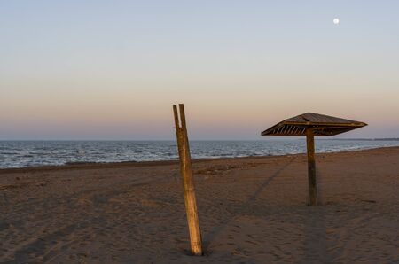 Caspian Sea with beach and wooden beach umbrella with Moon in the evening.