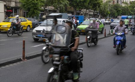 Teheran, Iran - May 21, 2019: Heavy traffic with cars, motorcycles and scooters in Teheran, Iran.