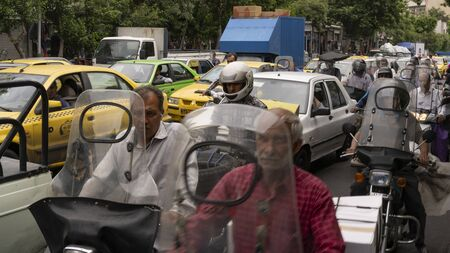 Teheran, Iran - May 21, 2019: Heavy traffic with cars, motorcycles and scooters in air polluted Teheran, Iran.