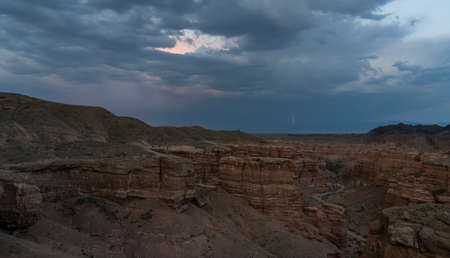 Panorama of Charyn Canyon National Park and dry and hot valley in Kazakhstan at night with thunder and lightning.