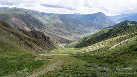Road on the Song Kol Pass in Kyrgyzstan with mountains and hills.
