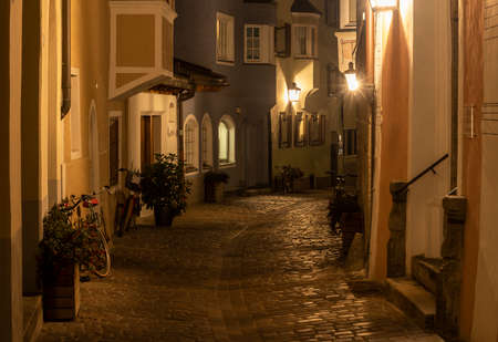 Brixen, Italy - October 9, 2020: City centre of Brixen at night with old, historical houses and street lanterns.
