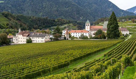 Brixen, Italy - October 9, 2020: The monastery of Abbazia di Novacella, Kloster Neustift, with vineyards in autumn, in the Dolomites, Italy.