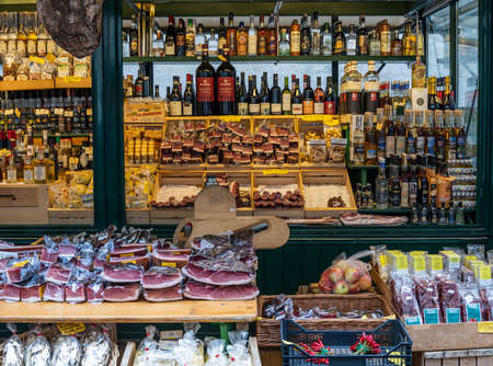 Brixen, Italy - October 4, 2020:   Market stall with delicacies such as meat and wines in Brixen in autumn with two salesman.