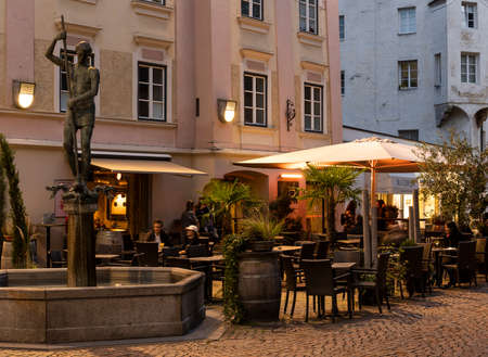 Brixen, Italy - October 9, 2020: City centre of Brixen at night with terrace and people and old, historical houses. 에디토리얼