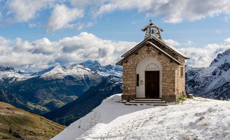 Bordoi Belluno, Italy - October 7, 2020: Chapel of Santa Maria Della Difesa in the snow on the pass of Bordoi Belluno in Trentino Alto Adige in the Dolomites in Italy.
