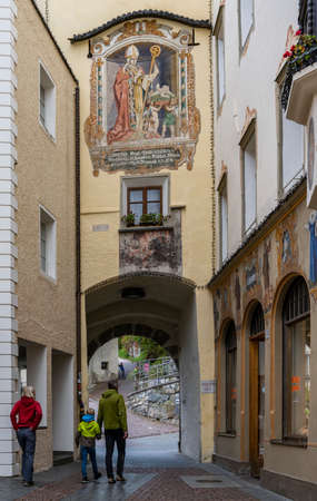 Bruneck, Italy - October 4, 2020: the city of Bruneck with old house and painting on wall and walking people in autumn. 에디토리얼