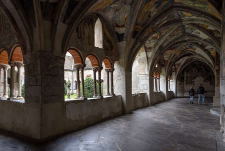 Brixen, Italy - October 5, 2020: Cloister with paintings, fresco, of the Cathedral of Brixen with roman architecture and visitors in autumn. 에디토리얼
