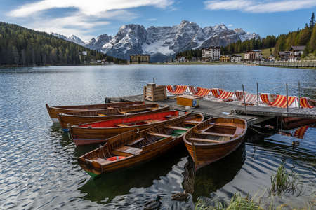 Misurina, Italy - October 8, 2020: The Misurina lake with tourist boats and hotels and snowy mountains of the Dolomites in the background, in autumn, Italy.