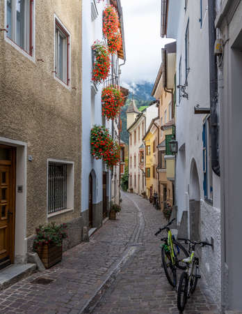 Brixen, Italy - October 5, 2020: Small street in the city of Brixen, Bressanone, with yellow houses in Italy, Sud-Tirol.