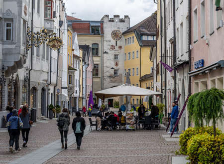 Bruneck, Italy - October 4, 2020: the city of Bruneck with terrace and shopping people in autumn.