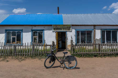 Numrug, Mogolia - August 10, 2019: Building, small houses, store at the road to Numrug with an old bicycle in front of the house on an unpaved road.
