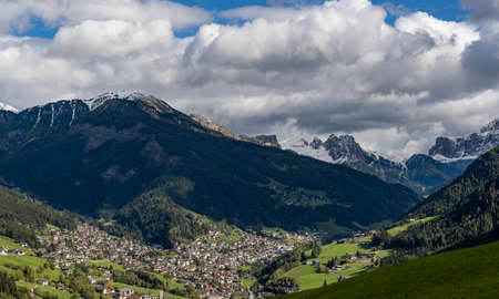 Sankt Ulrich, Italy - October 7, 2020: City of Sankt Ulrich in the valley Grödnertal with high snowy mountains of the Dolomites in Trentino, Italy
