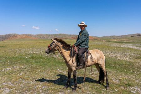 Tsagaanhairhan, Mongolia - August 9, 2019: Mongolian shepherd on horseback with hat and on the steppe of Mongolia.