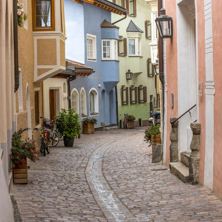Brixen, Italy - October 5, 2020: Small street in the city of Brixen, Bressanone, with yellow and blue houses in Italy, Sud-Tirol.