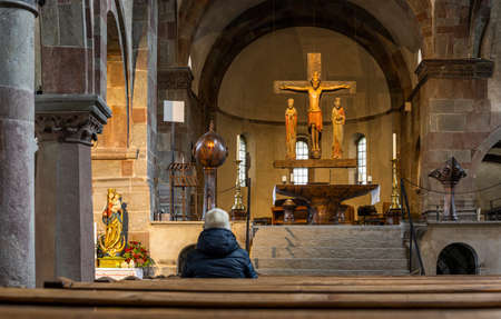 Innichen, Italy - October 4, 2020: Intirior of the Stiftskirche, church, of Innichen with old wooden roman crucifix and visitor sitting and praying in the church, Italy. 에디토리얼