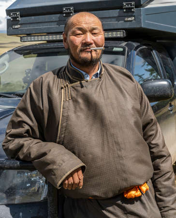 Tsagaan-Uul, Mongolia - August 11, 2019: Portrait of a Mongolian man in traditional clothes with cigarette in front of a car.