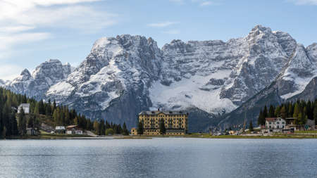 Misurina, Italy - October 8, 2020: The Misurina lake with Opera Diocesana San Bernardo and snowy mountains of the Dolomites in the background, in autumn, Italy. 에디토리얼