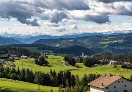 Kastleruth, Italy - October 7, 2020: View on Kastelruth with church and surrounded with forest and farms and in the background the mountains of the Dolomites, Italy. 에디토리얼