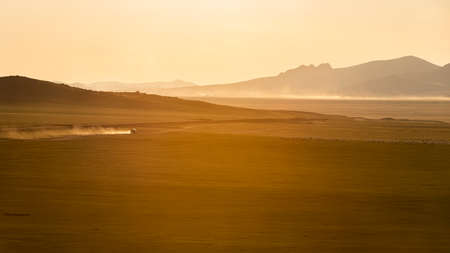 Sunset on the steppe of Mongolia with dust and moving car on an unpaved road and mountains in the background.