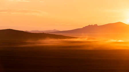 Golden yellow sunset on the steppe of Mongolia with moving car and dust and mountains in the background. 에디토리얼