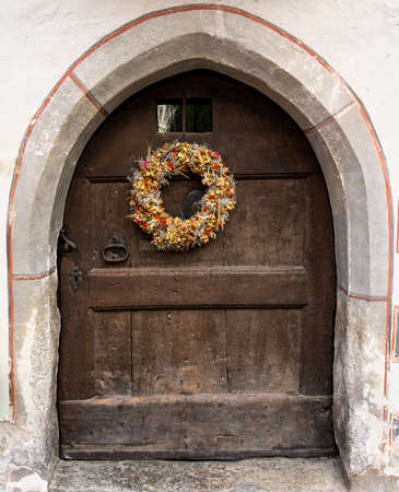 Autumn wreath with dreid flowers on an old wooden door.