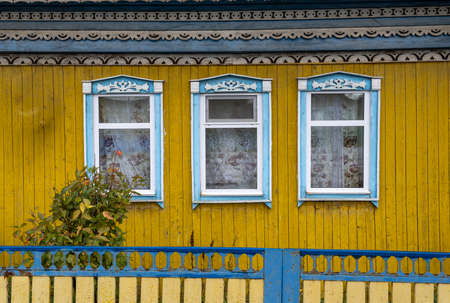 Old wooden log cabin and cottage in blue with flowers in Urals, Russia.