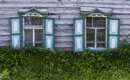 Russian old wooden white log cabin with light green and blue shutters in Krasnoyarsk, Siberia, Russia.
