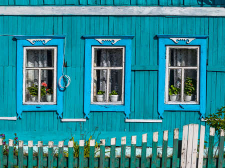 Russian old blue log cabin with green fence and some flowers in Tinskoy, Siberia, Russia.