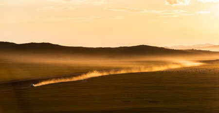 Sunset on the steppe of Mongolia with dust and moving car on an unpaved road and mountains in the background. Stock Photo