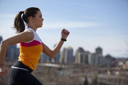 ジョグ: 都市公園で走っている若い女性