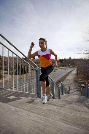 운동하는 동안 계단을 실행하는 젊은 여자