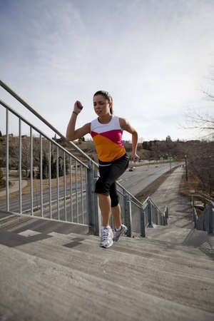 Young woman running up stairs during workout