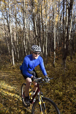 old people: Man mountain biking up trail in autumn