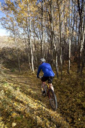 Man mountain biking down autumn trail photo