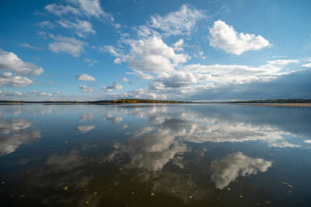 Lake level on an autumn afternoon. Reflecting cloudy sky. 免版税图像