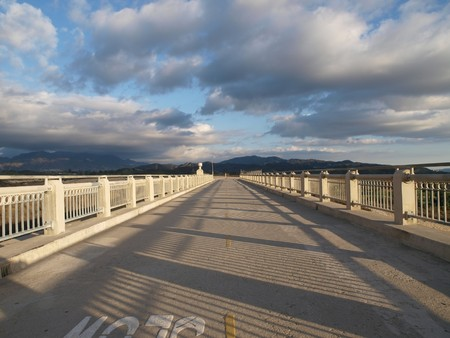 Open road with dramatic afternoon sky on top of flood control dam.  Stock Photo - 4295194