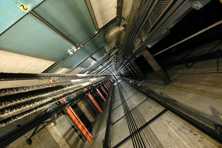 The view up inside a tall elevator shaft. Stock Photo